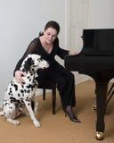 Musiker med hennes hund vid det stora pianot Royaltyfri Foto