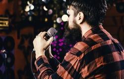 Musiker med sjungande sång för skägg i karaoke, bakre sikt Mannen i rutig skjorta rymmer mikrofonen, den sjungande sången, karaok arkivbild