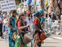 Musiker med tarbuks i mång--färgade dräkter deltar i karnevalet av Adloyada klädde, som spanar går med valsar i Nahar Royaltyfri Foto