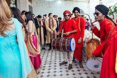 Musiker sätter band bärande röda Bandhgala och svart Pheta på indisk bröllopceremoni i Bangkok, Thailand fotografering för bildbyråer