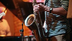 Musiker-saxofonist som spelar ett instrument på ett parti i en jazzstång i ramen endast hans händer arkivfilmer