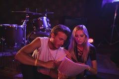 Musiker som öva med musikark i nattklubb Royaltyfri Fotografi