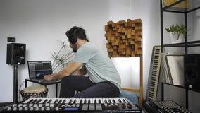 Musiker som arbetar i programvara i hem- musikstudio stock video