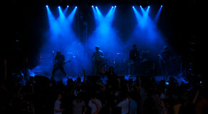 Musiker som framme spelar gitarren av en folkmassa av folk på en konsert på klubban Arkivbild