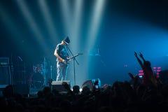 Musiker som framme spelar gitarren av en folkmassa av folk på en konsert på klubban Arkivfoton