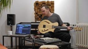 Musiker som pluggar i elektrisk gitarr i hem- musikstudio stock video