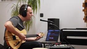Musiker som sjunger och spelar den elektriska gitarren i hem- musikstudio stock video