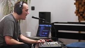 Musiker som sjunger och spelar det midi tangentbordet i hem- musikstudio lager videofilmer