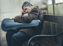 Musiker som sover på hans instrument på gatabänk Arkivbilder