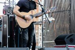 Musiker som spelar den akustiska gitarren på utomhus- etapp under levande Co Arkivbild