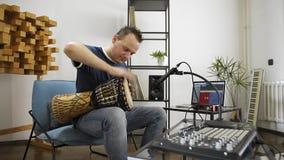 Musiker som spelar djembevalsinstrumentet i hem- musikstudio stock video