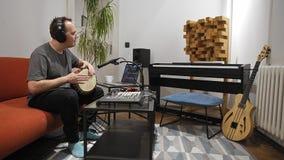 Musiker som spelar djembevalsinstrumentet i hem- musikstudio lager videofilmer