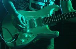 Musiker som spelar gitarren i en nattklubb royaltyfri fotografi