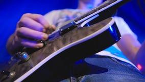 Musiker som spelar melodi för elektrisk gitarr Detaljer av raderna och assistent nära uppsamlingarna lager videofilmer
