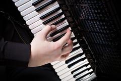 Musiker spielt das Akkordeon gegen einen dunklen Hintergrund Stockfotos