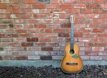 Musiker Takes ett avbrott - vägg för gitarr & för röd tegelsten Royaltyfri Foto