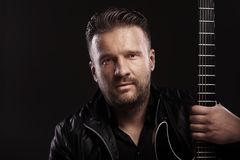 Musikermann sitzt mit Gitarre Stockfotografie