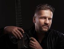 Musikermann sitzt mit Gitarre Stockfotos