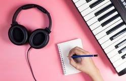 Musikern skriver på anteckningsboken med studiorosa färger Arkivfoto
