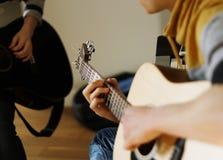 Musikern spelar en beiga för akustisk gitarr arkivbilder