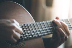 Musikern spelar en klassiska gitarr, fretboard och fingrar arkivbild