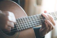 Musikern spelar en klassiska gitarr, fretboard och fingrar arkivbilder
