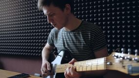 Musikern spelar på den electro gitarren i studion stock video