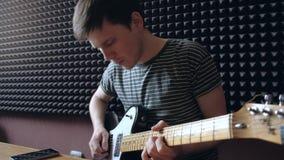 Musikern spelar på den electro gitarren i studion arkivfilmer