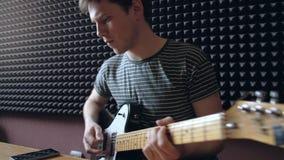 Musikern spelar på den electro gitarren i studion lager videofilmer