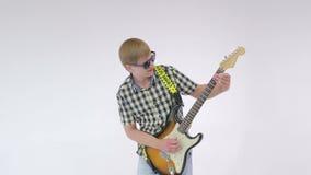 Musikerrocker spielt auf E-Gitarre, tanzt und krächzt am weißen Studiohintergrund stock video