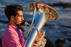Musikerspiel zur Tuba auf romantischem Seeufer relax stockbild