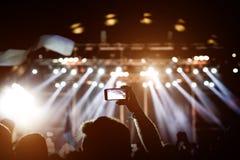 Musikfans tar bilden av etappen i konsert på smartphonen fotografering för bildbyråer