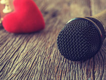 Musikfreundkonzept Ein schwarzes Mikrofon auf hölzerner Platte mit Re Stockfoto