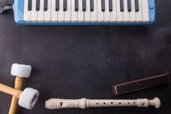 Musikinstrumentbakgrund med flöjten, pianika, munspelet och den bas- pinnen på svart trä arkivfoto