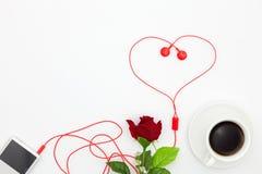 Musikspelare med den röda hörlur- och kaffekoppen, rosblomma på whi Fotografering för Bildbyråer