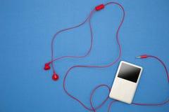 Musikspelare med den röda hörluren på bakgrund för blått papper Arkivbilder