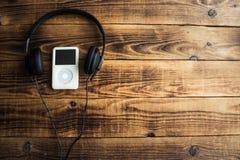 Musikspelare och hörlurar på en träbakgrund Fotografering för Bildbyråer