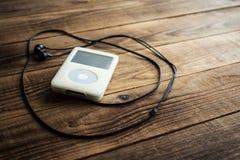 Musikspelare och hörlurar på en träbakgrund Arkivfoton
