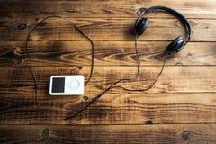 Musikspelare och hörlurar på en träbakgrund Royaltyfri Foto