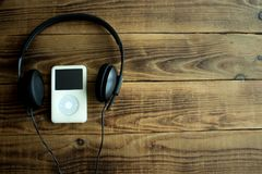 Musikspelare och hörlurar på en träbakgrund Royaltyfria Bilder