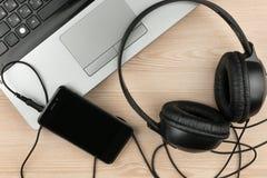 Musikstudio Bärbar dator, telefon och hörlurar på tabellen Arkivbild