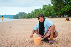 Musilim woman collecting shells on a beach. KRABI, THAILAND - 13 OCT 2014: Happy local muslim woman wearing her hijab collecting shells on Ao Nang beach to make Stock Images