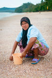 Musilim woman collecting shells on a beach. KRABI, THAILAND - 13 OCT 2014: Happy local muslim woman wearing her hijab collecting shells on Ao Nang beach to make Royalty Free Stock Photography