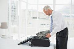 Musinessman déballant le bagage à une chambre à coucher d'hôtel Photos stock
