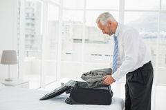 Musinessman uitpakkende bagage bij een hotelslaapkamer Stock Foto's