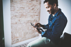 Musing bearded African American freelancer touching display of digital tablet while working in new project at home.Black. Businessman looking for information on stock image