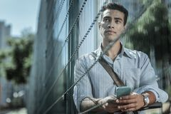 Musing handsome guy calling online on phone. Video call. Low angle of meditative attractive guy posing behind fence and carrying phone stock image