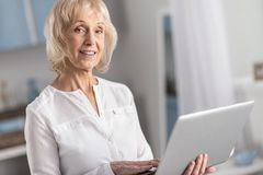 Musing mature woman studying online. Online education. Meditative doubtful mature woman smiling while staring at camera and using laptop stock photo