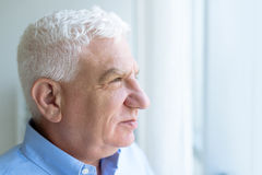 Musing. Portrait of a senior man looking through window stock images