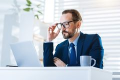 Musing reflective man examining report. Daily report. Meditative focused concentrated man touching glass  while wearing suit and staring at the screen Royalty Free Stock Photo